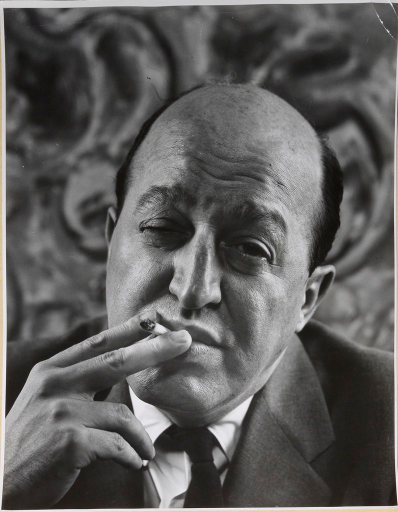 A black and white of critic Clement Greenberg raising his eyebrows