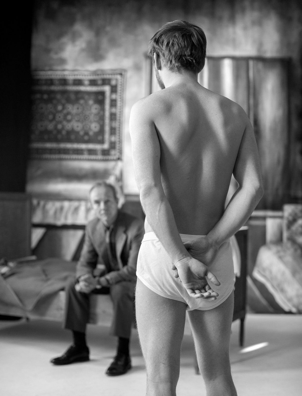 a young man stands half naked in front of a dressed old man