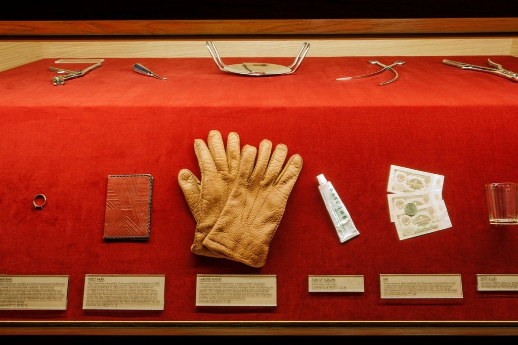 a museum display with some gloves, hand cream, the red book from the communist party