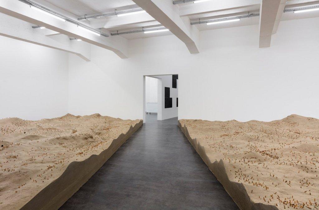 cigarette butts on large indoor sand dunes