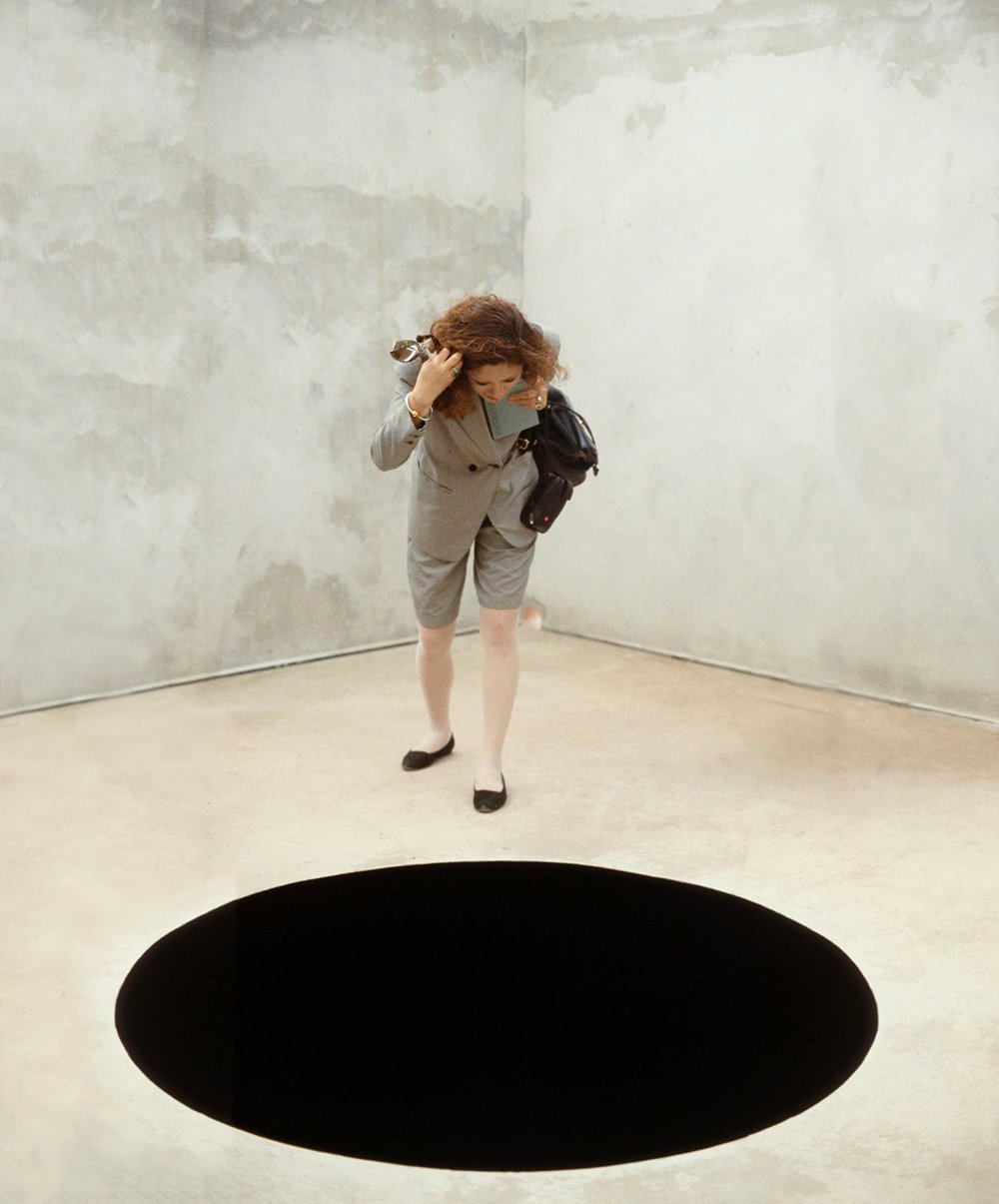 a woman stares into a black hole on the ground