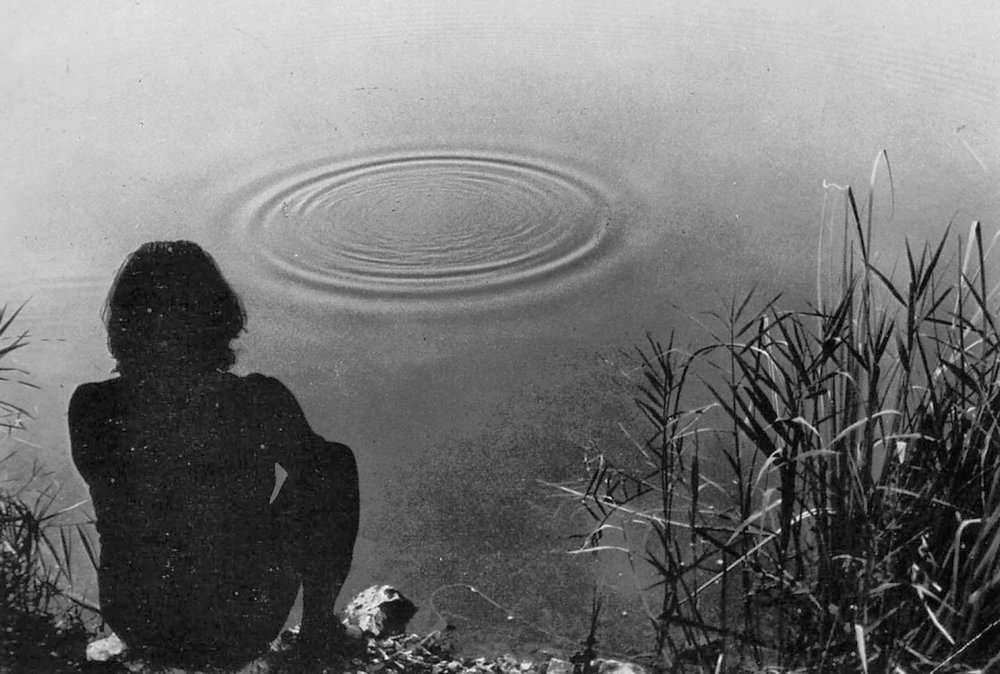 a man stares at some circles in the water